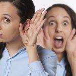 Una ragazza con la mano all'orecchio intenta ad ascoltare mentre dietro un'altra donna si porta le mani alla bocca urlando