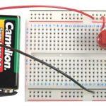Una piastrina di plastica forata con una batteria da 9volt collegata e sopra attaccati dei componenti elettronici (transistor, resistenze, LED)