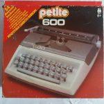 """Una scatola di cartone con la fotografia di una macchina da scrivere di plastica per bambini e la scritta """"petite 600"""""""