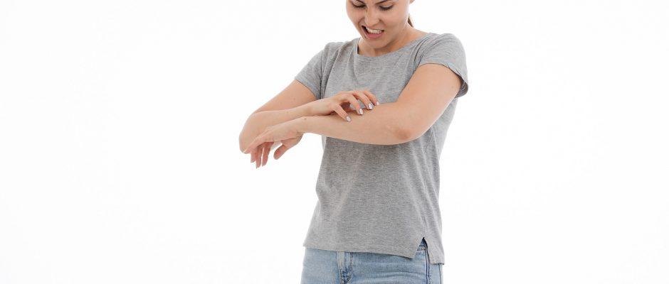 Una giovane donna grattandosi il braccio sinistro con aria infastidita