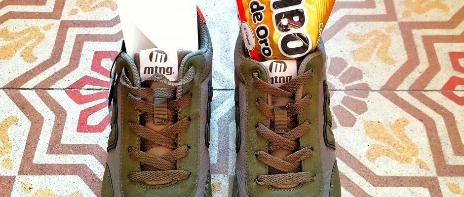 Un paio di scarpe nuove appoggiate per terra. In una c'è un bigliettino, nell'altra una confezione di caramelle gommose