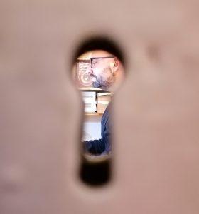 Una fotografia in cui mi si vede attraverso il buco della serratura mentre sono impegnato a scrivere