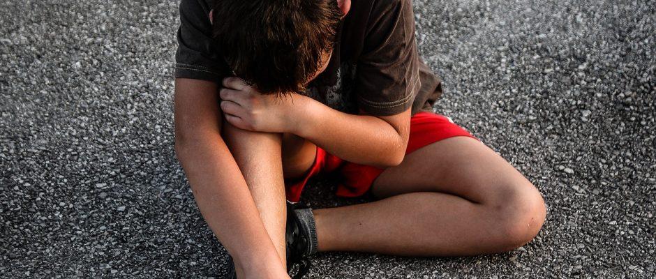 un bambino accovacciato sull'asfalto che si tiene il ginocchio con aria sofferente