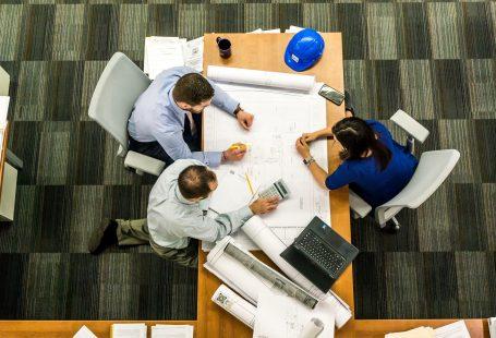 una riunione di lavoro: tre persone intorno a un tavolo fotografate dall'alto