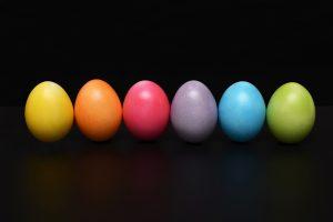 Sei uova di colori diversi messe in fila su sfondo nero