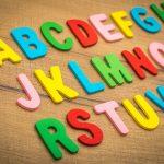 l'alfabeto scritto a lettere di plastica colorata appoggiate in tre file su una tavola di legno