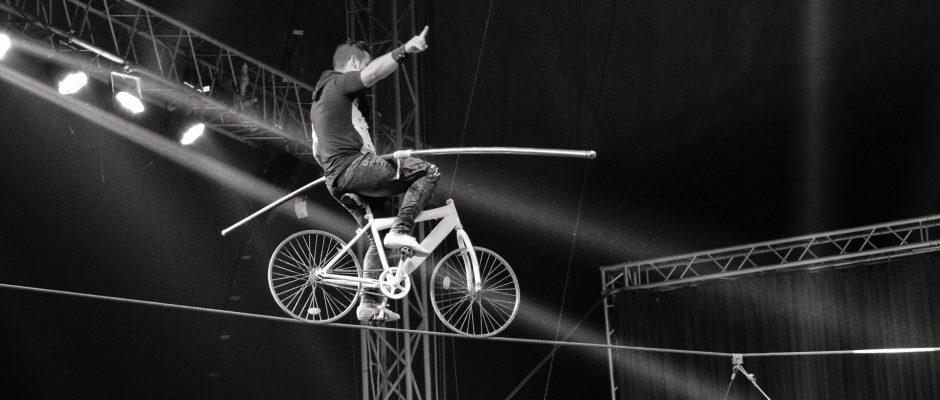 Acrobata su una corda in bicicletta