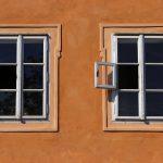 due finestre, una accanto all'altra, esattamente uguali su una parete arancione